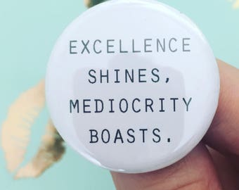 excellence shines, mediocrity boasts.1.25 inch pinback button. let your good works speak for themselves!