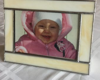Stained glass photo frame in light cream or butterscotch browns holds a 4 x 6 photo