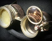 Steampunk goggles in dark brown leather and brass with dark moveable lens, golden mesh and embossed decoration.