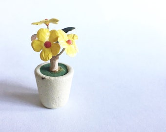 teeny tiny potted yellow and red flowers in white pot