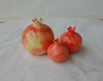 3 ceramic pomegranates in red orange hues,