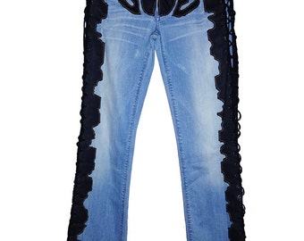 A pair of vintage light blue jeans with side black velvet hand stiched and lace up
