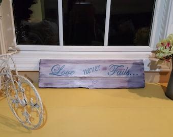 "Love Never Fails- wood sign 6""H X 20W"""
