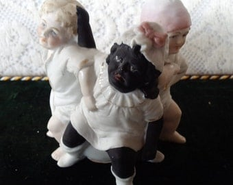 Three black and white children fighting for seat on potty pot bisque figurine