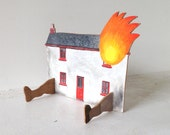 A little hand painted house on fire wearing slippers