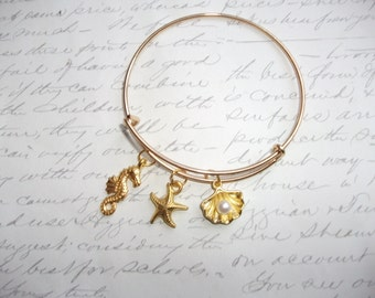 Seahorse starfish and and seashell charm gold bangle bracelet