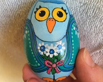 Wooden Blue and teal hand painted Owl egg holding blue centered white daisies tied with pink bow