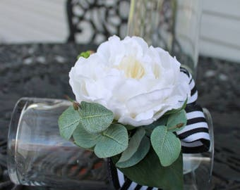 White peony wrist corsage with real touch ficus leaves and eucalyptus. Black and white stripped ribbon.