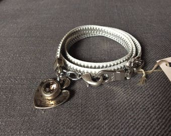 A zipper with a heart made of silver and rhinestone pendant bracelet