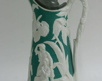 Victorian Parian type jug decorated in raised relief with a pewter lid, impressed marks to the base,