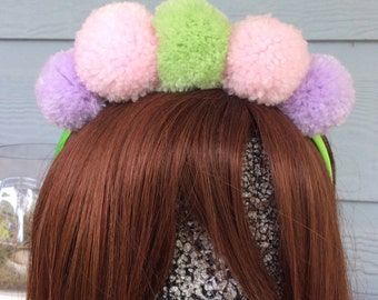 Pastel coloured babies headband on a lime green satin headband