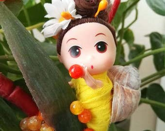 Small doll dressed as snails mum on flower.