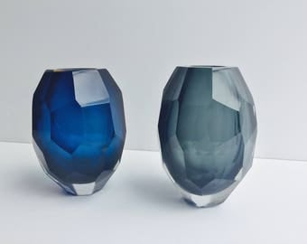 A decorative glass vase in blue with geometrical multi surfaces
