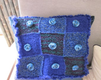 Handknitted patchwork wool and mohair cushion cover, with knitted roses and crochet trim.