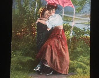 """Vintage Postcard """"It's Raining Very Heavy Here Still"""" - 1907 featuring an adorable couple holding an umbrella"""