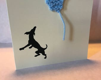 Playful dog chasing hand knitted balloon