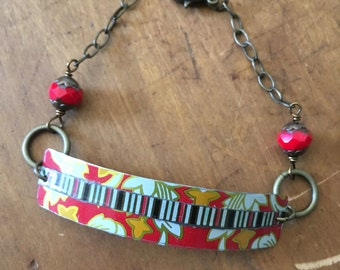 Red, yellow, and black vintage tin collage bracelet