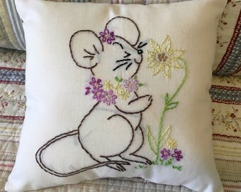 Upcycled embroidery, mouse smelling flowers, cottage chic, porch pillow, ticking purple, yellow, green, shelf