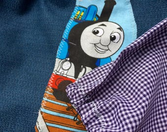 Toddler's long sleeve waterproof art smock, age 2-3 years. Dark blue with train motif.