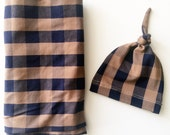 Baby boy swaddle blanket and hat set. Tan and navy buffalo check blanket with a matching knot hat.