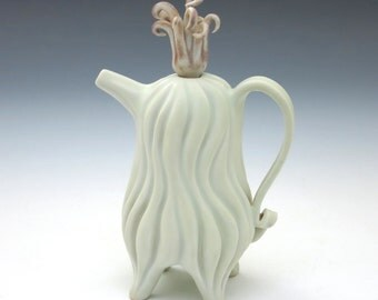 Curvy pale yellow porcelain teapot with curly dark pink lid