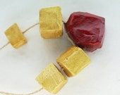 The idea of deserving -- a set of 4 large golden faceted beads and large red jewel pendant