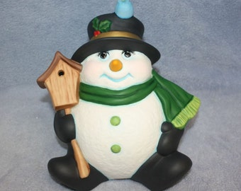 Ceramic Snowman sitting back in a top hat and green scarf and birdhouse with a bluebird on top of his head