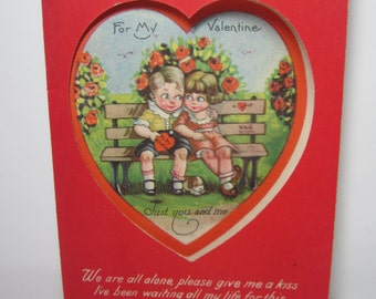 1920's-30's adorable die cut heart window valentine card shows big eyed little boy and girl on park bench and a puppy sleeping at their feet