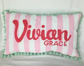 Baby pillow with light pink stripes and hot pink lettering.