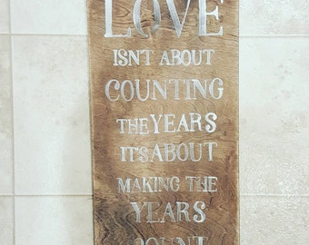 Love isn't about counting the years wooden sign