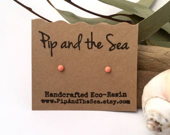 New improved waterproof design! Itty bitty, peach eco-resin studs, on allergy-friendly surgical steel.