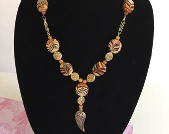 Gold Toned Metal Brown Swirled Bead Necklace - Angel Wing Necklace - Tan Gold and Brown Bead Necklace with Gold Toned Metal Accents
