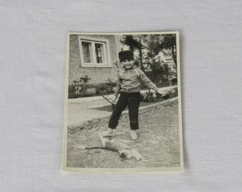 Vintage black and white photo of a happy boy playing with a cat, black and white photo, Vintage photo, Funny vintage photo, vintage photo.