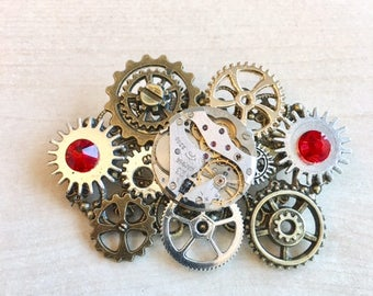 Steampunk pin with watch mechanism, gears and Red Swarovski Crystal