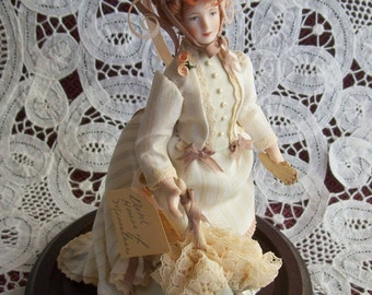 One Inch Scale Porcelain Doll with Glass Dome made by Beverly Dahl in 1987.