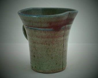 A stoneware studio pottery coffee mug by Keith Smith of Otterton Mill Pottery Devon. Altered form mug in clear glaze with subtle highlights