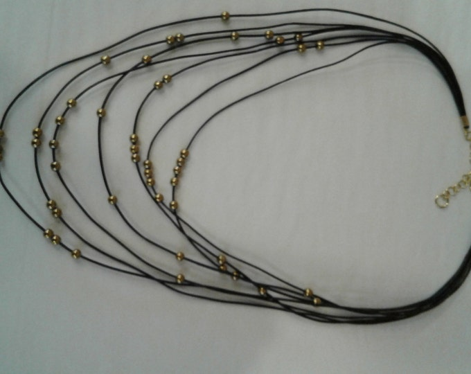Necklace made of black leather strand and gold colored hematite beads.
