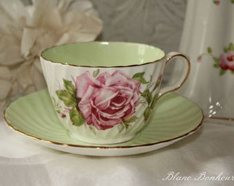 Aynsley, England: White and mint green tea cup & saucer, with a large pink rose