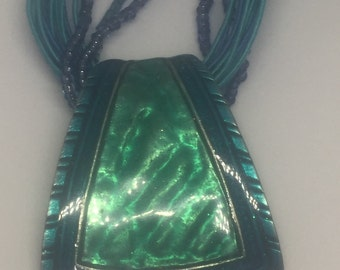 Enamelled pendant on lace and beaded string