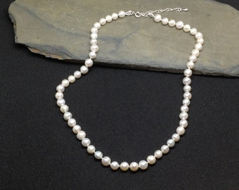 A white ,cultured pearl, knotted necklace with 925 sterling silver.