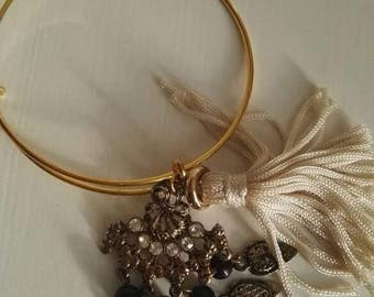 Rigid bracelet with charms and tassel