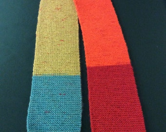 """Knit scarf from Caron Cakes Yarn """"Rainbow Sprinkles"""" (teal, red, ornge, gold, green)."""