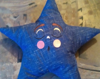 Star cushion with embroidered face, sleeping