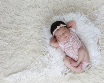 Newborn Baby photography prop lace romper in peach with peach bow at the back pretty patterning cap style sleeves scoop neck and low back.