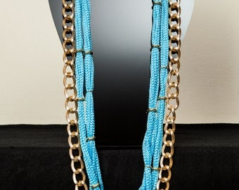 Turquoise cord and gold chain necklace.