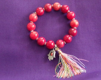 B125 Red glass  beaded bracelet with Tassle and Charm.