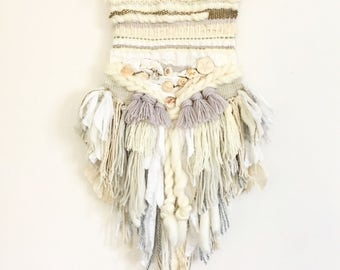 Weaving wall hanging, tassel, shells and fringe woven with rustic branch of wood
