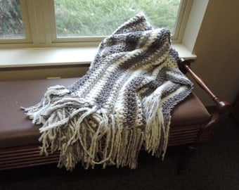 gray and white crocheted throw with fringe.