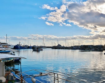 A fishing harbor at sunset. A long view of the calm Mediterranean with the blue sky reflected in the water.