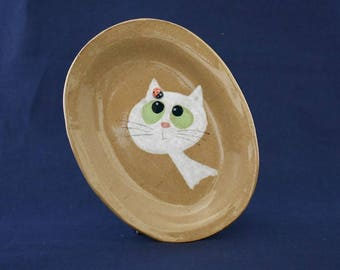 White fluffy cat and ladybug plate